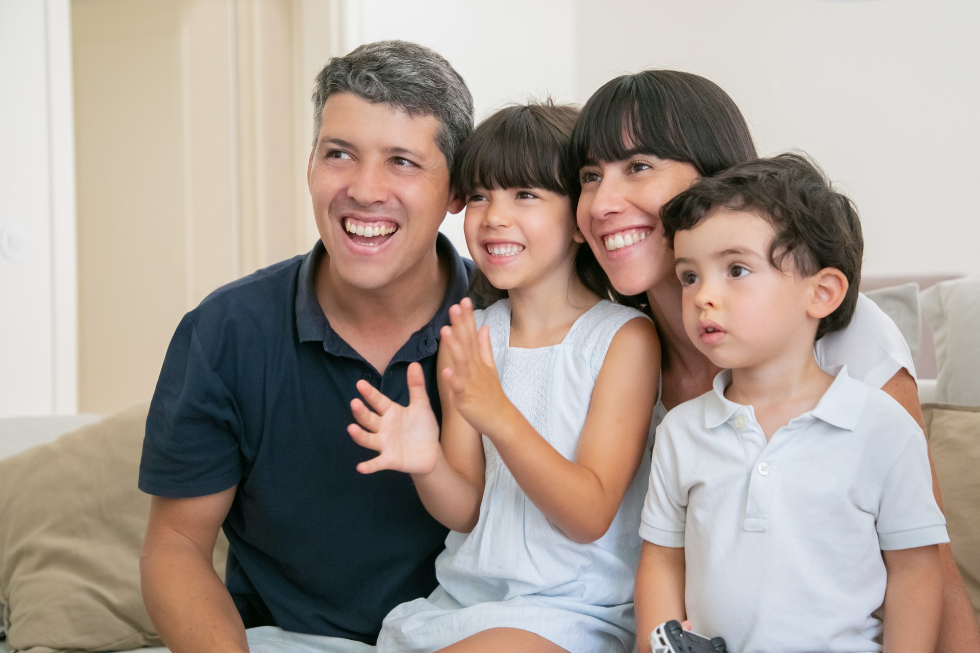 excited joyful parent couple with two kids watching tv sitting on couch in living room looking away and smiling