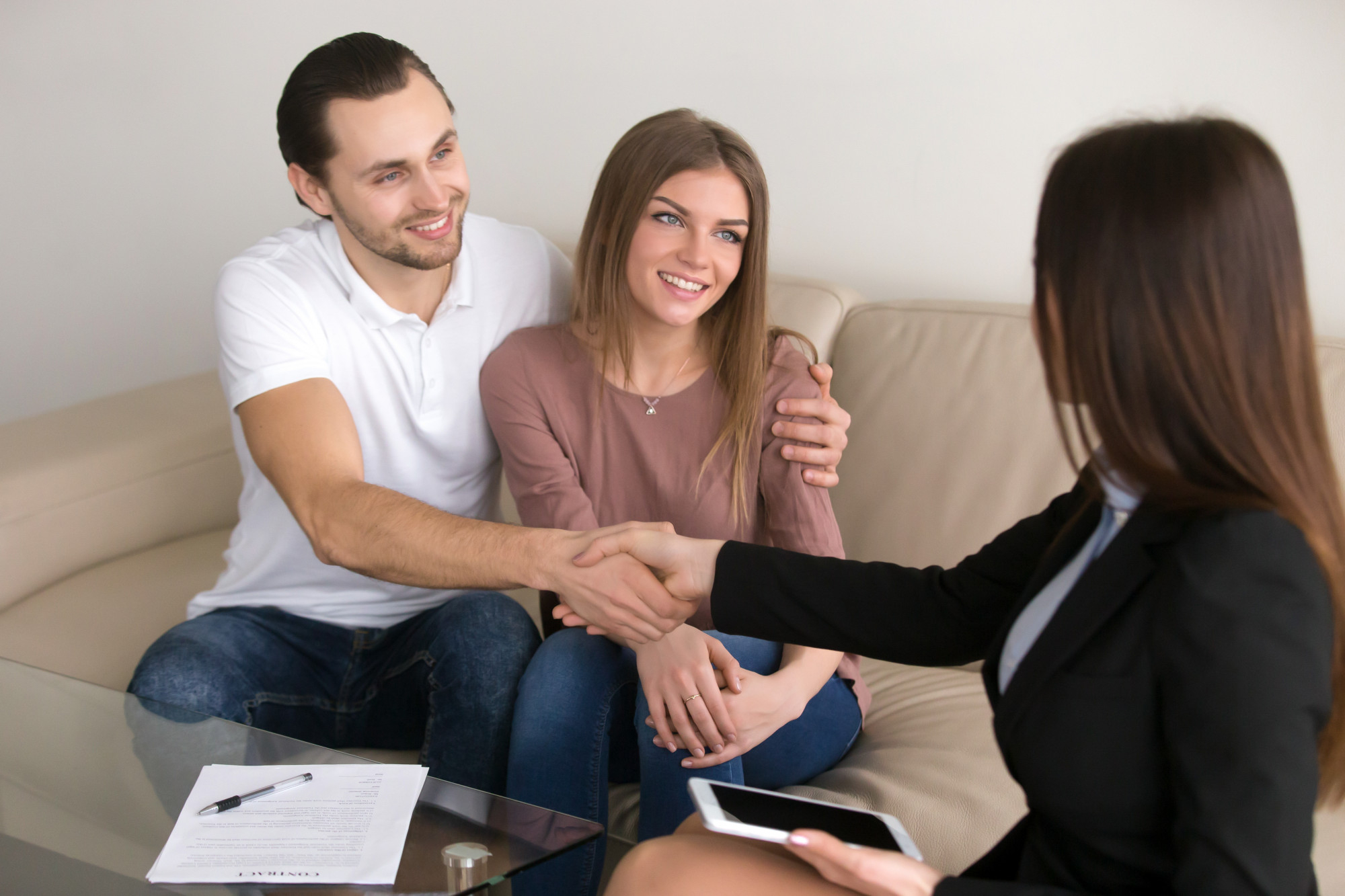 happy young couple and broker manager handshaking after signing contract